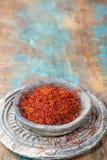 Especiaria vermelha orgânica secada do açafrão em uma bacia de pedra no backgr de madeira Imagem de Stock Royalty Free