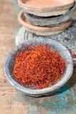 Especiaria vermelha orgânica secada do açafrão em uma bacia de pedra no backgr de madeira Imagens de Stock Royalty Free