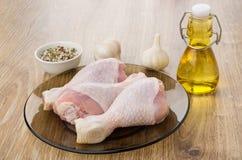 Especiarias, alho, garrafa do óleo e pés de galinha crus Imagem de Stock Royalty Free