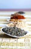 Especiarias coloridas em um tabela-fundamento da palha Foto de Stock Royalty Free