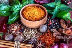 Especiarias e ervas aromáticas coloridas em um backgrownd marrom de madeira Imagens de Stock Royalty Free