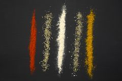 Especiarias e ervas diferentes em um preto Imagem de Stock