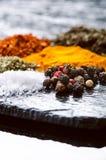 Especiarias e ervas diferentes em uma ardósia preta Especiarias indianas Ingredientes para cozinhar Conceito saudável comer Vária Imagem de Stock Royalty Free
