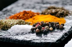 Especiarias e ervas diferentes em uma ardósia preta Especiarias indianas Ingredientes para cozinhar Conceito saudável comer Vária Fotos de Stock Royalty Free
