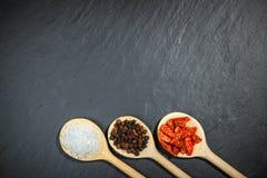 Especiarias em colheres de madeira sobre o fundo de pedra preto foto de stock