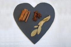 Especiarias em uma ardósia dada forma coração Imagens de Stock Royalty Free
