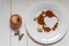 Especiarias em uma placa especiarias da pimenta da cebola do alho na forma de um coração foto de stock