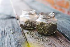 Especiarias secadas nos frascos de vidro na tabela de madeira foto de stock royalty free