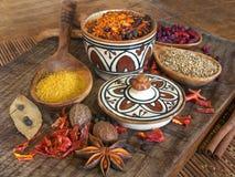 Especiarias secas na placa de madeira e na cerâmica africana Imagem de Stock Royalty Free