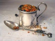 Especiarias secas no copo e na colher da prata do vintage no fundo do linho Foto de Stock