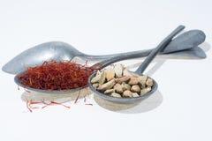 Especiarias vermelhas orgânicas cruas do açafrão e do cardamomo em colheres velhas da lata sobre Imagens de Stock