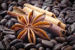 Especias; anís de estrella, canela en el fondo de los granos de café foto de archivo