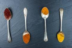 Especias coloridas en vintage, cucharas viejas Paprika, curry, azafrán y otro en un fondo negro Fotografía de archivo libre de regalías