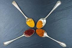 Especias coloridas en vintage, cucharas viejas Paprika, curry, azafrán y otro en un fondo negro fotos de archivo