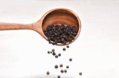 Especias de la pimienta negra en cuchara de madera Fotografía de archivo