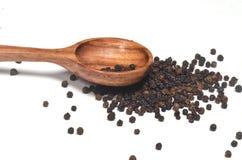 Especias de la pimienta negra en cuchara de madera Fotos de archivo libres de regalías