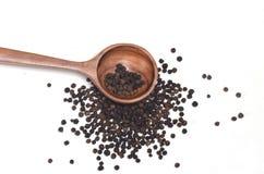 Especias de la pimienta negra en cuchara de madera Fotografía de archivo libre de regalías