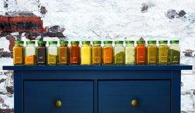 Especias de tierra clasificadas en botellas en la madera, aún vida con la especia Foto de archivo libre de regalías