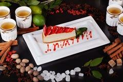 Especias del pastel de queso de la fresa, té, canela, nuez moscada moscada, fresas, aún vida apetitosa, menta, azúcar, tazas de t Imagen de archivo