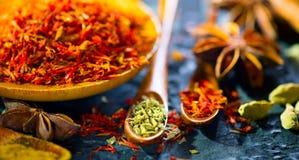Especias Diversas especias indias en la tabla de piedra negra Especia e hierbas en fondo de la pizarra cooking imagenes de archivo