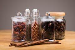 especias en las botellas de cristal en fondo de madera Imagen de archivo libre de regalías