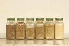 Especias en los tarros de cristal en un fondo ligero en la cocina Albahaca, or?gano, hierbas italianas copie el espacio para su t imagen de archivo libre de regalías