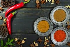 Especias indias coloridas en la sobremesa de madera negra Foto de archivo