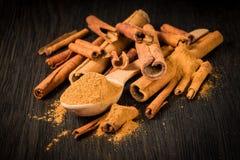 Especias; palillos y tierra de canela en una cuchara de madera en un fondo oscuro foto de archivo