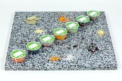 Especias secadas en envases de plástico en un fondo de mármol Fotos de archivo