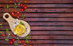 Especias, tomates de cereza, albahaca y aceite vegetal en la tabla de madera oscura, visión superior imagenes de archivo