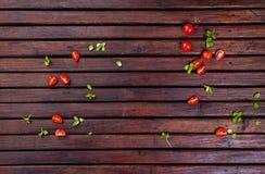 Especias, tomates de cereza, albahaca y aceite vegetal en la tabla de madera oscura, visión superior imágenes de archivo libres de regalías