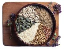 Especias y semillas en cuenco de cerámica condimento Anuncio natural colorido Imagenes de archivo