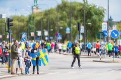 Espectadores con los trajes suecos y finlandeses que animan en el funcionamiento foto de archivo