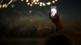 Espectadores con smartphones Fotografíe el fuego artificial en el teléfono, manos del primer metrajes