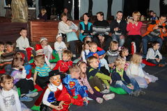 Espectadores de teatro jovenes niños que miran entusiasta el teatro Smeshariki del espectáculo de marionetas de la Navidad de los Fotos de archivo libres de regalías
