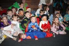 Espectadores de teatro jovenes niños que miran entusiasta el teatro Smeshariki del espectáculo de marionetas de la Navidad de los Imagenes de archivo