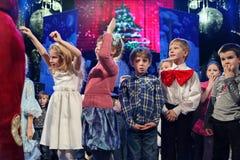 Espectadores de teatro jovenes niños que miran entusiasta el teatro Smeshariki del espectáculo de marionetas de la Navidad de los Imágenes de archivo libres de regalías