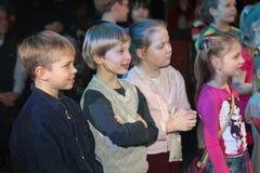 Espectadores de teatro jovenes niños que miran entusiasta el teatro Smeshariki del espectáculo de marionetas de la Navidad de los Foto de archivo