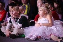 Espectadores de teatro jovenes niños que miran entusiasta el teatro Smeshariki del espectáculo de marionetas de la Navidad de los Foto de archivo libre de regalías