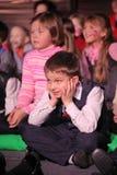 Espectadores de teatro jovenes niños que miran entusiasta el teatro Smeshariki del espectáculo de marionetas de la Navidad de los Imagen de archivo