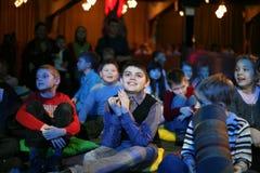 Espectadores de teatro jovenes niños que miran entusiasta el teatro Smeshariki del espectáculo de marionetas de la Navidad de los Fotografía de archivo libre de regalías