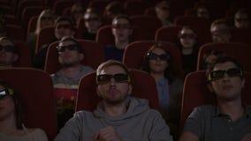Espectadores nos vidros 3d que olham o filme no cinema Povos nos vidros 3d vídeos de arquivo