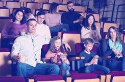Espectadores numerosos que comen las palomitas en el cine Imágenes de archivo libres de regalías