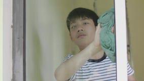 Espejo asiático joven de la limpieza del muchacho en casa almacen de metraje de vídeo