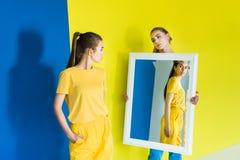 Espejo atractivo de la tenencia de la chica joven para su amigo en azul fotografía de archivo