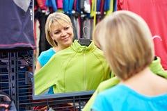 Espejo cercano de la mujer feliz que intenta para la ropa de deportes en tienda Foto de archivo