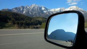 Espejo de ala del coche y tráfico por carretera y montañas Imagenes de archivo