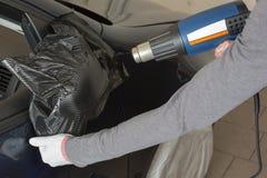 Espejo de coche envuelto en hoja adhesiva o película por el coche que envuelve al especialista imágenes de archivo libres de regalías