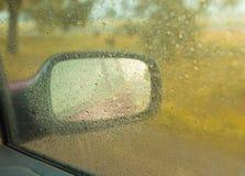 Espejo de coche visto a través de la ventanilla del coche mojada fotos de archivo