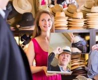 Espejo de la tenencia de la mujer y cliente de la demostración su reflexión en sombreros imagen de archivo
